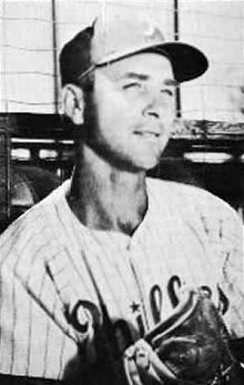 A black-and-white image of a man wearing a pinstriped baseball uniform and a dark-colored baseball cap