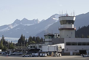 Juneau International Airport - Closeup view of the airport's main terminal, including both older and newer control towers.  Mendenhall Glacier is seen in the background.
