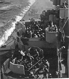 A kamikaze (just left of center near the top border), a Mitsubishi Zero in this case, about to hit the Missouri.