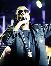 A man holding a microphone and wearing white sunglasses, black clothing and a chain around his neck.