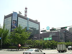 Four-story MBC headquarters, with trees in foreground