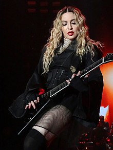 Madonna plays guitar whilst performing on stage