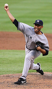 Mariano Rivera in a gray baseball uniform and navy blue cap stands on a dirt mound. He is striding forward to the left as he holds a baseball in his forward-extended right arm. His face is contorted in concentration.