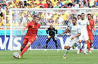 Riyad Mahrez - Mahrez (right) playing for Algeria against Belgium at the 2014 FIFA World Cup.