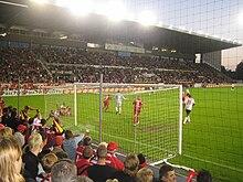 Photo d'un match de football prise depuis la tribune basse derrière le côté droit des buts.