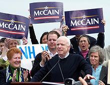 """Blankhara viro parolante ĉe podio, kun grupo de homoj malantaŭ li, iujn tenante bluajn """"McCain"""" signojn"""