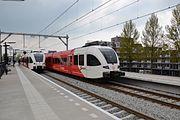 Twee treinen die elkaar kruisen op Dordrecht Stadspolders.