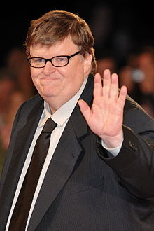 A mean wearing glasses and a suit waves to the camera and smiles slightly.