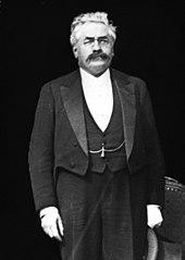 Zwart-witfoto van een staande man, met wit haar, een donkere snor, bril, een driedelig pak, een hoed in zijn hand