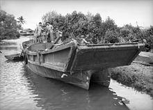 Четверо мужчин без рубашки на большой барже, пришвартованной на берегу реки.  Баржа имеет аппарель в носовой части корпуса, напоминающего катамаран.