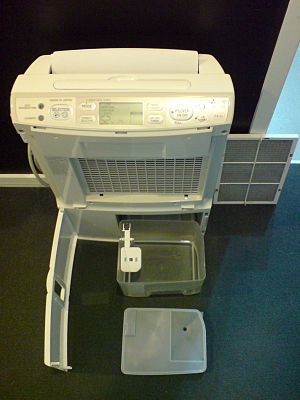 Dehumidifier - Partially disassembled portable dehumidifier, with condensate bucket and white-colored float sensor visible at center