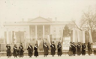 "National Woman's Party - NWP members picket the White House during the Silent Sentinels protests in 1917; the banner reads, ""Mr. President, How Long Must Women Wait For Liberty."""