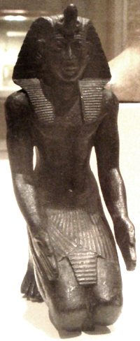A small kneeling bronze statuette, likely Necho II, now residing in the Brooklyn Museum