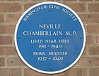 """Round blue plaque on a brick wall. It says """"BIRMINGHAM CIVIC SOCIETY"""", """"NEVILLE CHAMBERLAIN M.P."""", """"LIVED NEAR HERE 1911–1940"""", """"PRIME MINISTER 1937–1940""""."""