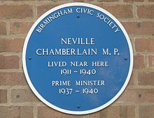 "Round blue plaque on a brick wall. It says ""BIRMINGHAM CIVIC SOCIETY"", ""NEVILLE CHAMBERLAIN M.P."", ""LIVED NEAR HERE 1911–1940"", ""PRIME MINISTER 1937–1940""."