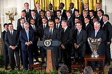 A group of soccer players for Sporting Kansas City dressed in suits behind President Barack Obama, who stands at a podium. The MLS Cup trophy stands to the President's left on a table.