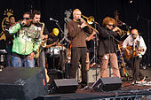 In the left a black man with sunglasses and a green jacket holding performing to a microphone beside him another man playing the saxophone, in the center blonde haired man playing the trombone and in the back a man with sunglasses and a yellow hat playing the percussion with his head down, and in the right a man with curly hair with sunglasses playing the trumpet beside him a bald man playing the guitar.