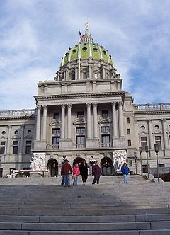 Looking up from a large, stone staircase is a marble facade of a building with a large, pale green dome. Several people are walking down the stairs.