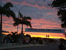 "A street in Parelhas, with palm trees and buildings, and a banner stating ""150 Anos"" (150 years) across the street, at sunset"