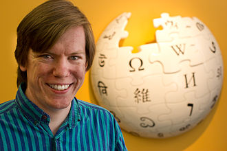 Wikipedia logo - Logo creator Paul Stansifer at the Wikimedia Foundation in front of the Wikipedia Puzzle Globe Logo sculpture in May 2012