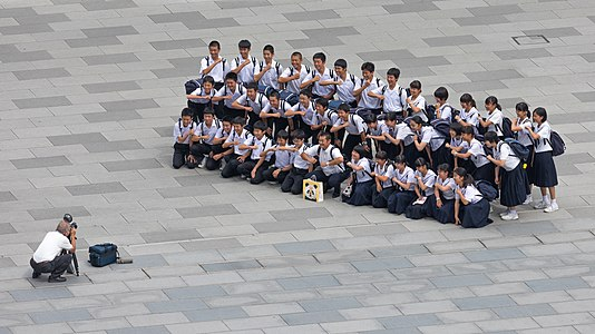 Photographer taking a group photograph of smiling students in front of the Tokyo station, Marunouchi, Japan