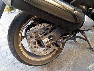 Yamaha TMAX - 4th Generation TMAX rear wheel, showing hydraulic brake caliper and parking brake mechanism on disc