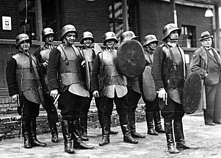 Polish riot police squad in the 1930s, with opaque riot shields and no helmet visors, as polycarbonate had not been invented yet Polish State Police (Policja Panstwowa) before 1939.JPG