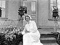 Porträtt av en kvinna i vit klänning och hätta sittande i trappan till ett bostadshus - Nordiska Museet - NMA.0056436.jpg