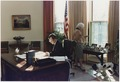 President Bush works at his desk in the Oval Office as Mrs. Bush looks at photographs on the table behind the Oval... - NARA - 186389.tif