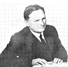 black and white photo of a seated man whose hands are on a book