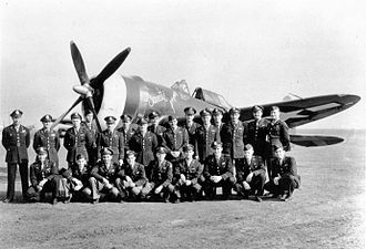 """RAF Bodney - Pilots of the 486th Fighter Squadron, 352nd Fighter Group, in front of P-47 Thunderbolt (PZ-R, serial number 42-8412), named """"Sweetie"""" at Bodney air base in March 1944."""