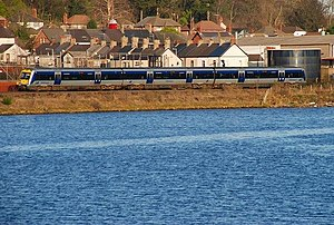 Larne Harbour railway station - A C3K train running on the Larne Line alongside Larne Lough heading towards Larne Harbour.