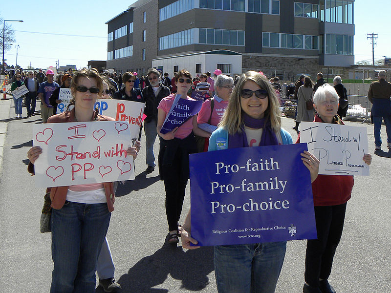 People march in a parade to support Planned Parenthood. A woman carries a blue sign with the words