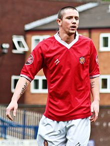 Rory Patterson in red F.C. United home kit playing on pitch, in front of brick buildings.