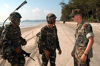 Royal Malay Regiment - Construction Mechanic 3rd Class Michael Klinegardner, a member of the Beachmaster Unit (BMU) One, detachment Western Pacific's craft control team, explains his role in landing craft, air cushioned (LCAC) operations to landing force members of the Royal Malay Regiment (RMR)