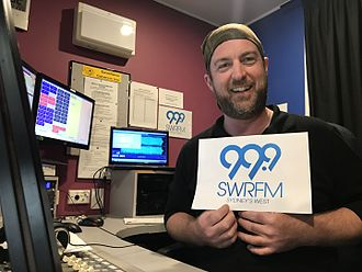 SWR FM - SWR Triple 9's breakfast announcer, Busco, holding the new logo.