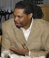 Photo couleur : Sam Perkins en costume assis à une table de restaurant s'exprimant paume de la main gauche levée