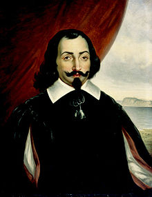 A half-length portrait of a man, set against a background that is a red curtain to the left and a landscape scene to the right. The man has medium-length dark hair, with a goatee and a wide mustache that is crooked up at the ends. He is wearing a white shirt with a wide collar, covered by a darker surcoat. There is also a bright red cape.
