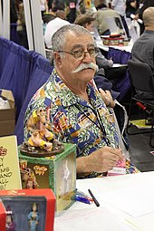 A man with thinning, greying hair and a thick, white moustache sits behind a table. He wears a colourful shirt. Pens and action figures of his works are on the table in front of him.