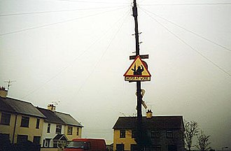 """South Armagh Sniper (1990–1997) - A """"Sniper at Work"""" sign in Crossmaglen"""