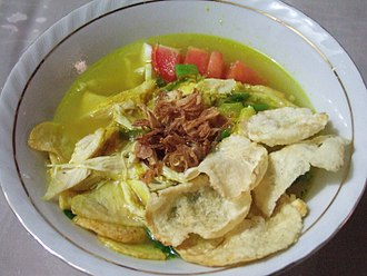 Soto (food) - Soto ayam with clear yellow broth, garnished with emping crackers and fried shallot.