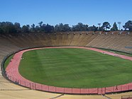 A view of Stanford Stadium from the stands, showing the pitch encircled by a running track