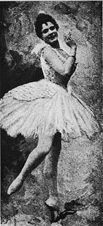 Old black and white photo of a ballerina posing en pointe in a tutu