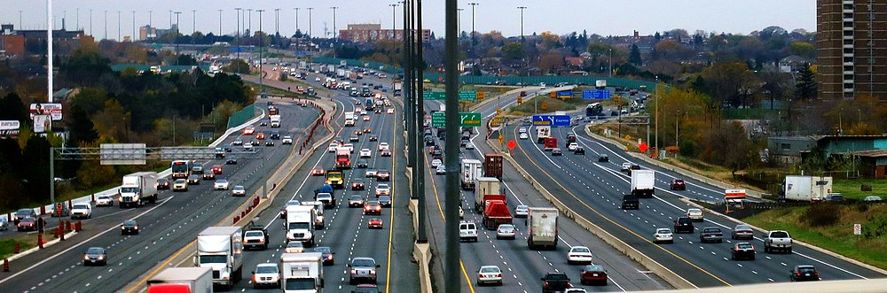 A wide angle image of Highway 401 completely occupied by cars. A city, Toronto, surrounds the freeway, but is walled off from it by green noise barriers. Each direction on the freeway is divided into two sets of lanes, referred to as a collector-express system.