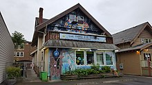 """Photograph of a building's exterior, which is covered in colorful murals and has a sign displaying """"The Third Eye Shoppe"""" in the center"""