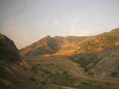 View through a dirty window, showing power lines in the foreground and a scarred mountain with the scar leading to an earthen dam.