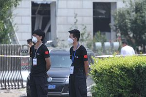 2015 Tianjin explosions - Two security inspectors wearing dust masks near the barricade tape off the scene