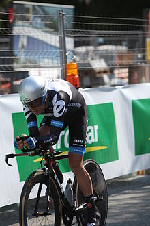 A road racing cyclist in a black and white skinsuit with blue trim and an aerodynamic helmet sits crouched low on his bicycle. There is a guardrail in the background.