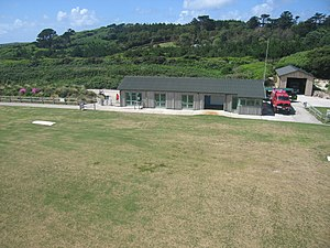 Tresco Heliport - The terminal building, with part of the island's famous Abbey Gardens in the background