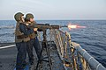 U.S. Navy Gunner's Mate 2nd Class Whitney Gutierrez, background, observes Engineman 2nd Class Cherrilyn Alonzo fire a M240B machine gun during a live-fire exercise aboard the guided missile destroyer USS Stout 140104-N-UD469-491.jpg